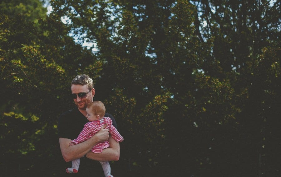 A man holds his baby daughter close to his chest in front of a large bush in the gardens at Cowley Manor Estate