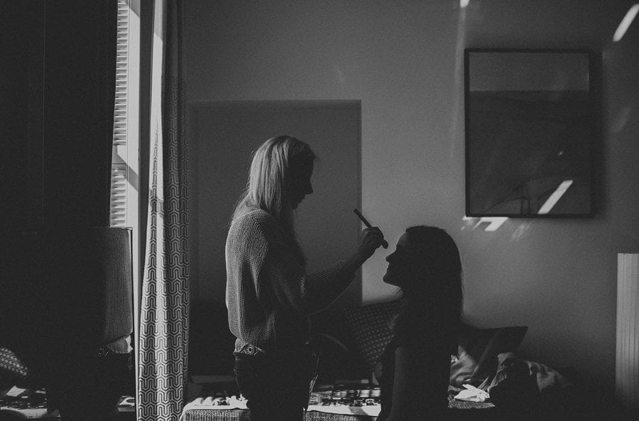 A makeup artist stands over a bridesmaid and brushes her nose with foundation