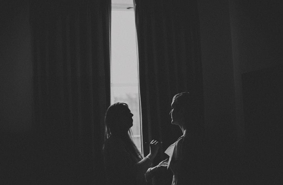 The makeup artist looks at the brides face in front of a large curtain next to a window at Cowley Manor