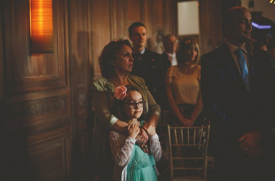 A flower girl stands and watches the wedding ceremony in front of her mother