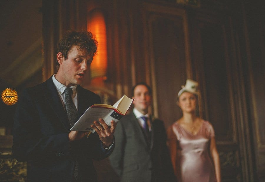 A wedding guest stands in front of the bride and groom and reads a poem during the wedding ceremony at Cowley Manor Hotel in Cheltenham