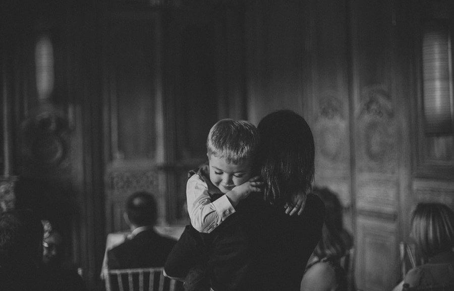 A little boy closes his eyes and puts his head on his mothers shoulder as she carries him across a room at Cowley Manor