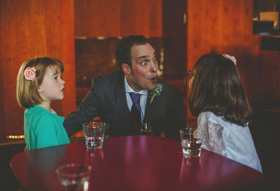 The groom looks startled as he looks at one of the children