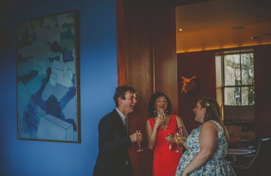 Wedding guests drinking champagne chat amongst themselves at Cowley Manor