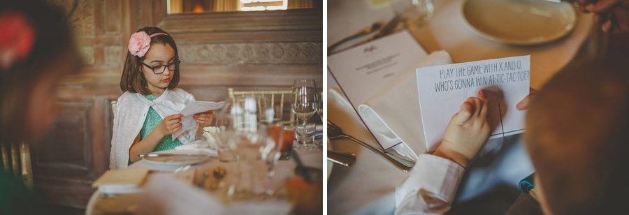 A flower girl reads the menu as she sits at the wedding table