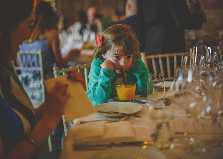 A little girl sits in a chair and sips a drink from a straw on the wedding table at Cowley Manor