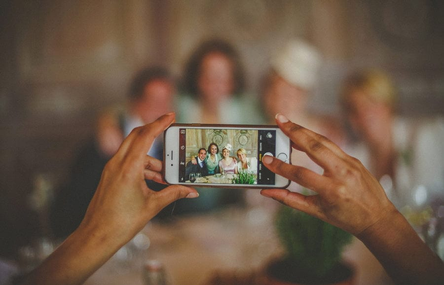 A wedding guest takes a photograph of the bride and groom on a mobile phone