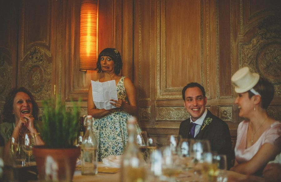 A bridesmaid stands in front of the wedding guests and delivers her speech as the groom smiles at the bride
