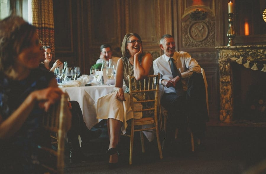 Wedding guests sat on chairs next to a table laugh at the speeches