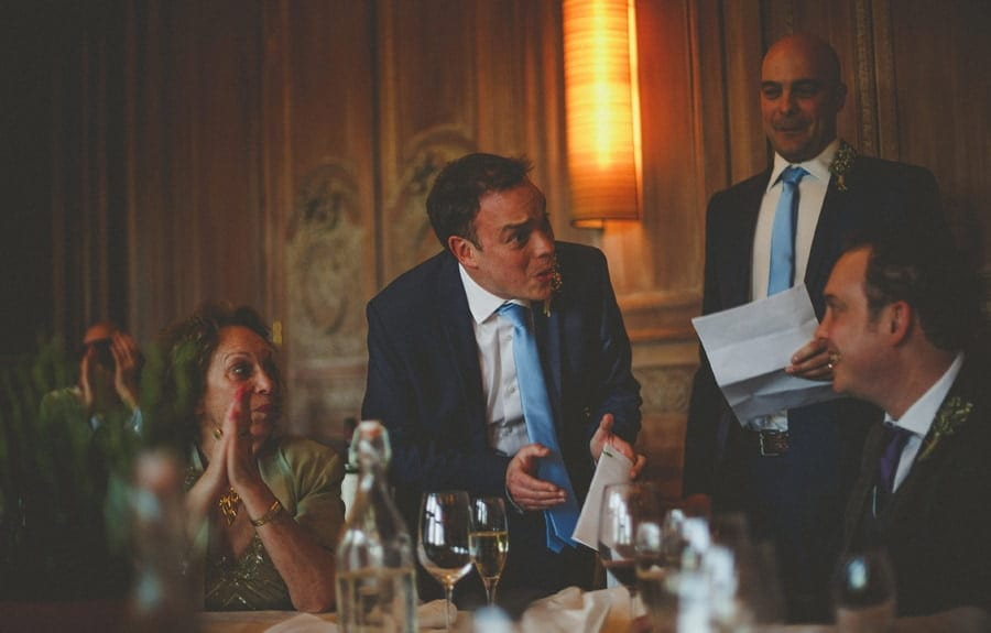 The groom standing up in front of the wedding table delivers his wedding speech at Cowley Manor