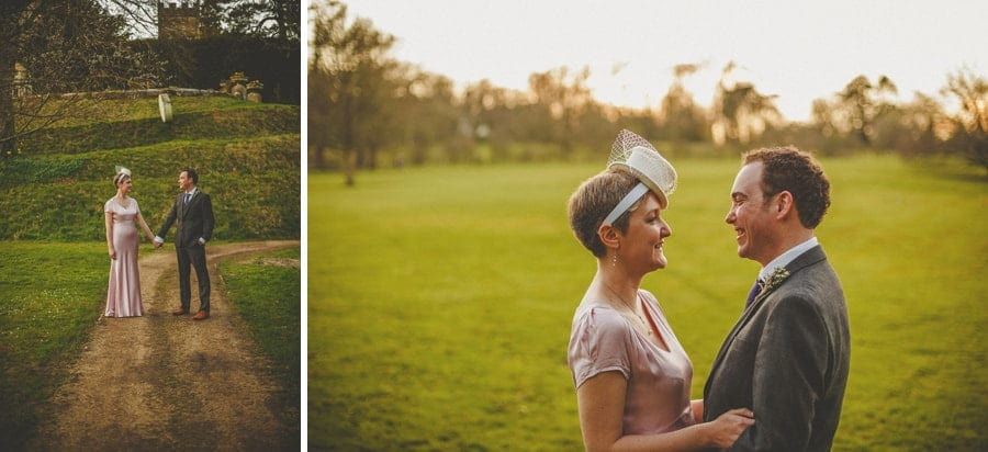 The bride and groom stand face to face with each other and pose for photographs on a field at Cowley Manor Estate.