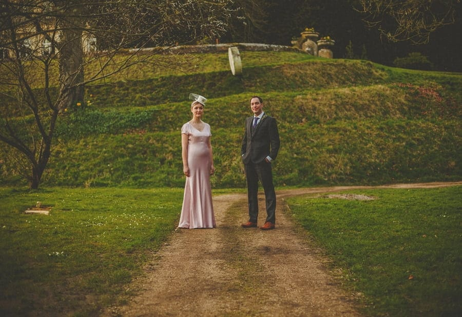 The bride and groom stand next to each other and pose for a photograph at the back of Cowley Manor Estate