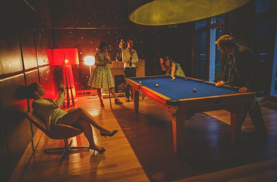 A lady sat in a chair next to the pool table takes a photograph on her mobile phone of wedding guests playing pool at Cowley Manor Hotel in Cheltenham