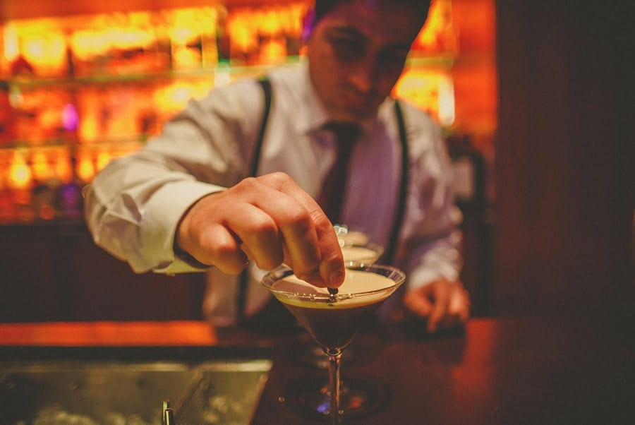 A bar man places a coffee bean into a cocktail drink on the bar