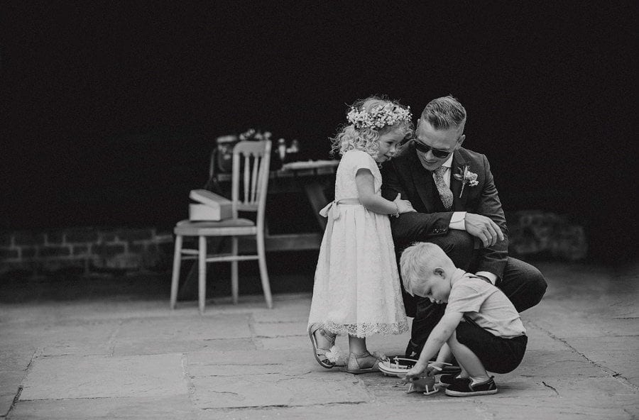 The groom kneels down and listens to his daughter in a courtyard with a little boy in front of them playing with a toy helicopter