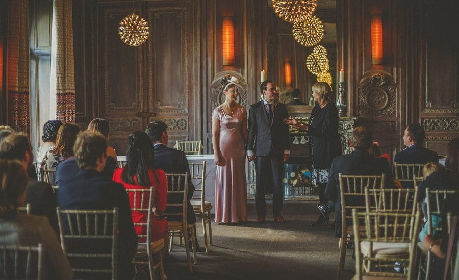 The bride and groom stand next to each other and listen to the registrar during the wedding ceremony at Cowley Manor Hotel