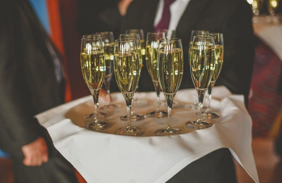 A tray of flutes filled with champagne is held by a waiter