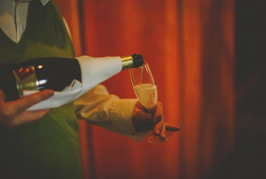 Champagne is poured into a flute by a waiter at Cowley Manor