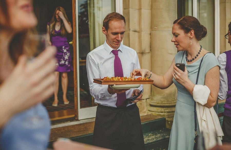A wedding guest takes a canape from a tray held by a waiter in the gardens at Cowley Manor Hotel in Cheltenham