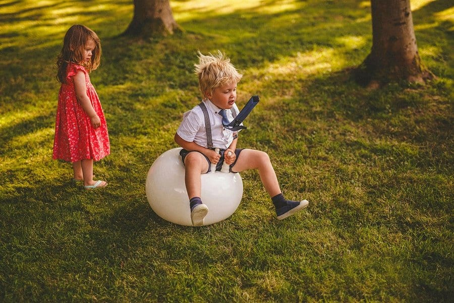 A little boy bounces on a space hopper in a field as a little girl with a red dress on watches him