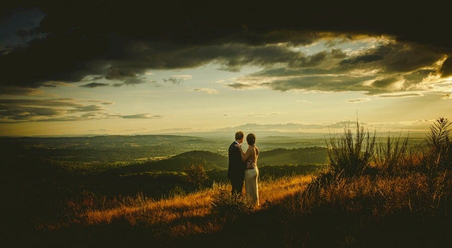 The bride and groom stand next to each other on top of a hill and look towards the distant hills as the sun goes down