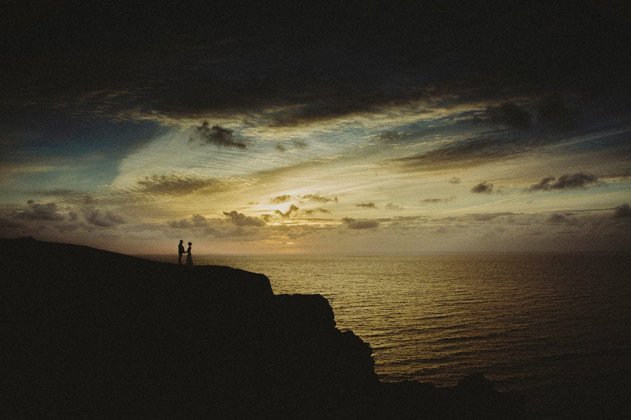 The bride and groom stand on the edge of a cliff next to the sea as the sun sets in the background