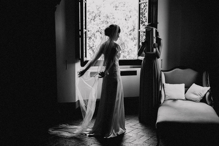 A bridesmaid holds a mirror up as the bride looks at herself as she stands next to a large window