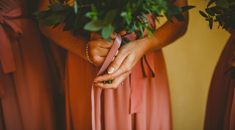 A bridesmaid holds her bouquet of flowers in both hands