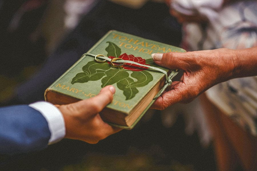 A book is passed from one guest to another with wedding rings strapped onto the front cover
