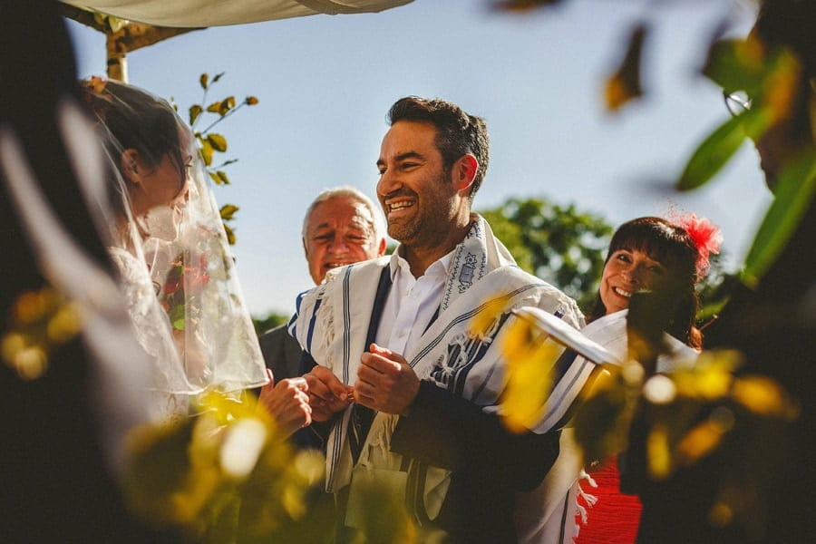 A groom stands in front of the bride and smiles as he holds a wedding ring during the outdoor wedding ceremony