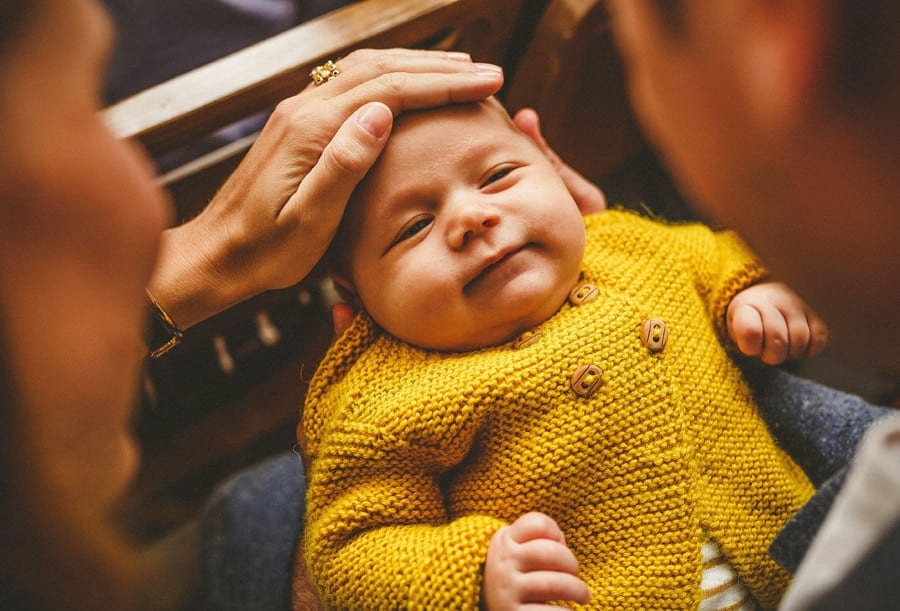 A lady puts her hand over the forehead of a baby boy as his mother holds him on her lap