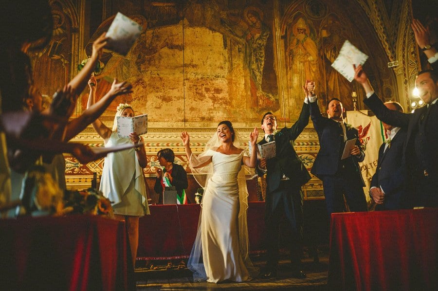 A bride and groom hold their hands up in the air and sing next to wedding guests during the wedding ceremony
