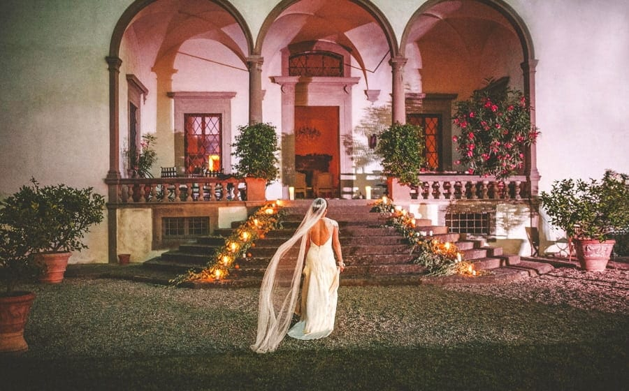 The bride walks towards stone steps as her veil is moved by the wind