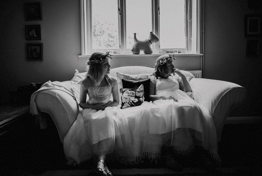 Two flower girls sit on a sofa