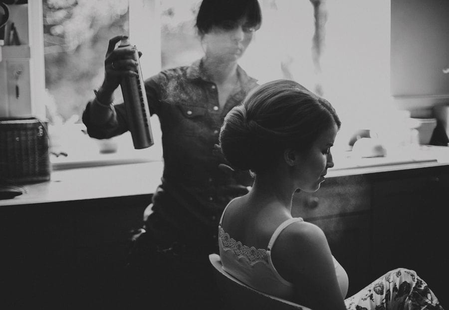 The make up artist sprays hair spray onto the brides hair