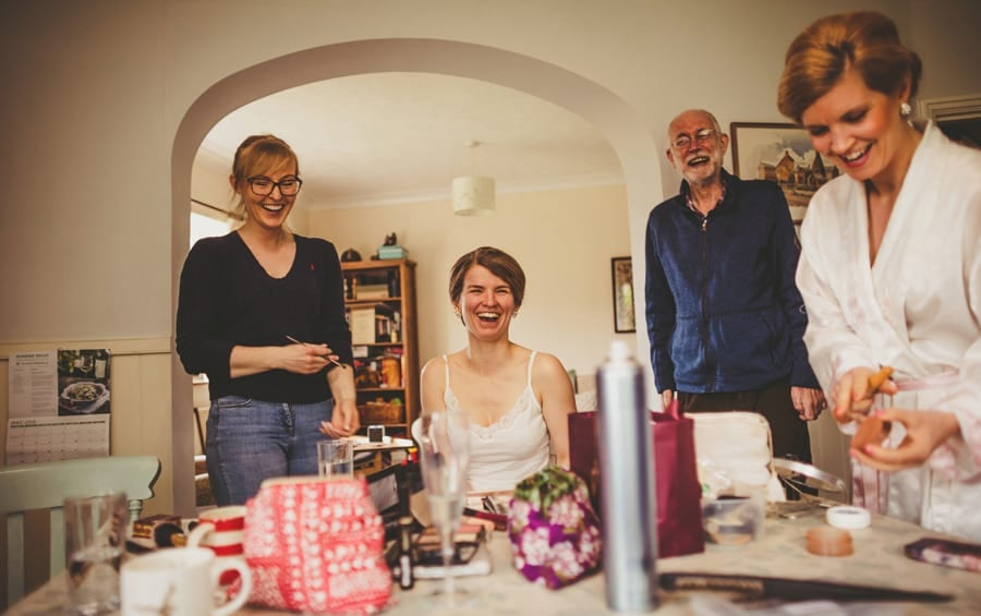 The bride laughs with her family in the kitchen of her parents house
