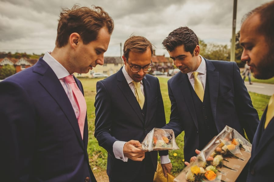 The groom and his ushers look at flowers fastened to a piece of cardboard
