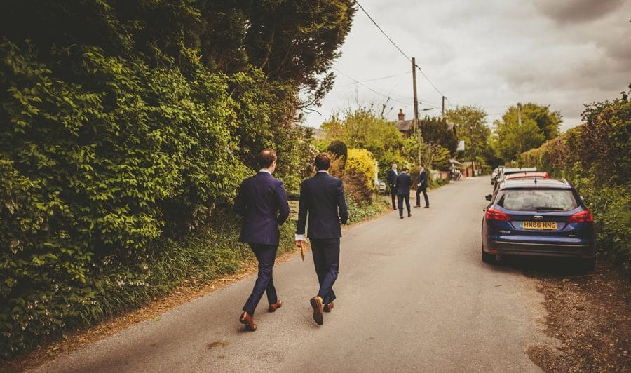 The groom and the ushers walk down a small road