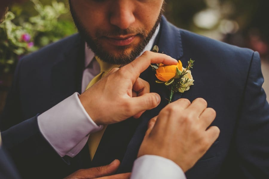 The groom fastens a flower to an ushers suit jacket