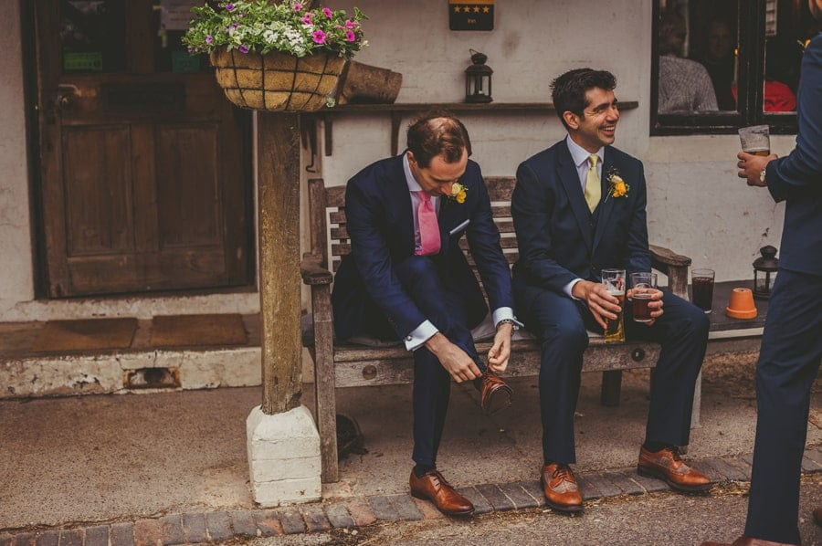 The groom sits on a wooden bench outside a public house and ties his shoelaces