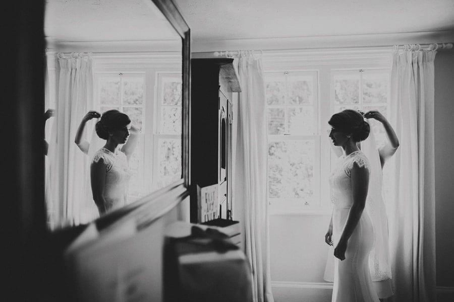 The bride looks in a mirror as her sister places her veil on the brides head
