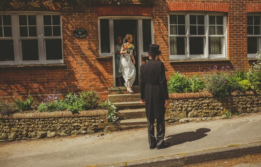 The brides father waits outside his house and the bride leave the house and walks down the steps
