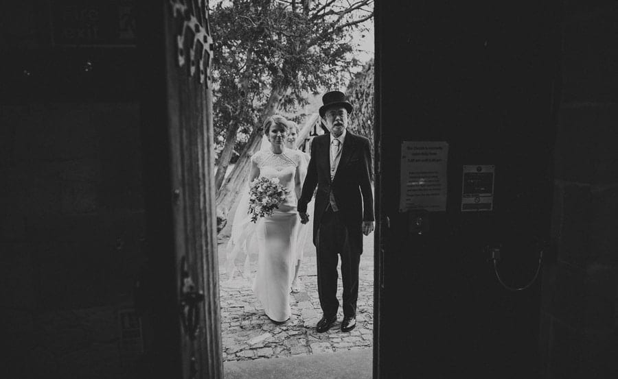The bride and her father stand at the door of the church and wait to go in
