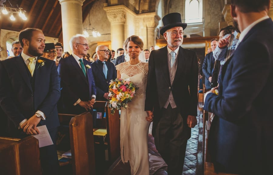 The bride and her father walk down the aisle of the church and are greeted by friends and family