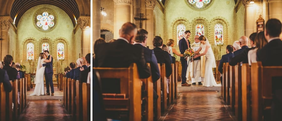 The bride and groom hold each other and kiss in the church during the wedding ceremony