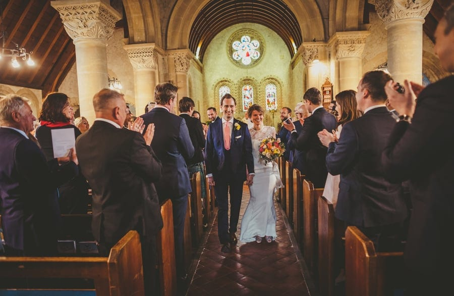 The bride and groom walk down the aisle of the church together as wedding guests stand and applaud