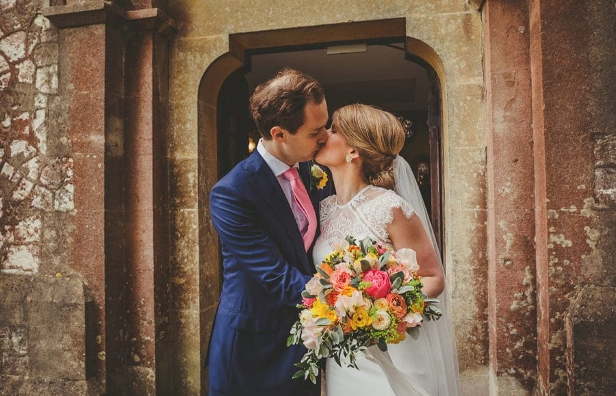 The bride and groom kiss each other outside the church
