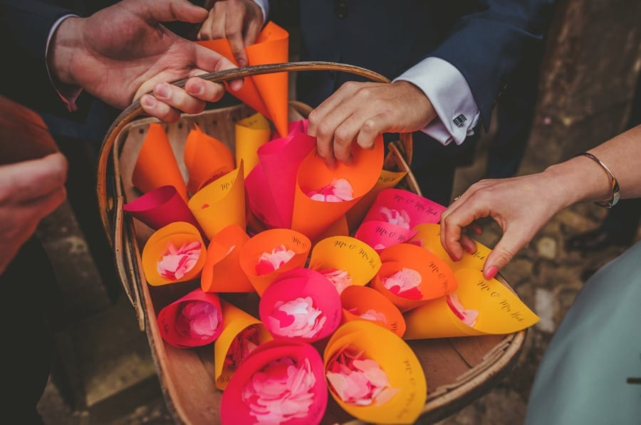Wedding guests pick up paper cones from a wicker basket