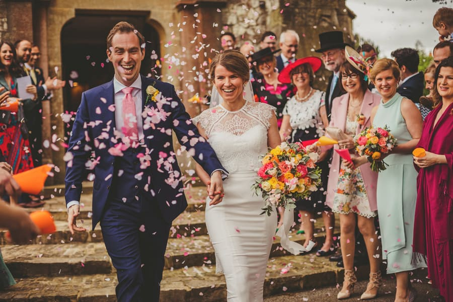 The bride and groom leave the church and are showered in confetti which is thrown by the wedding guests
