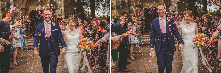 The bride and groom are covered in confetti outside the church